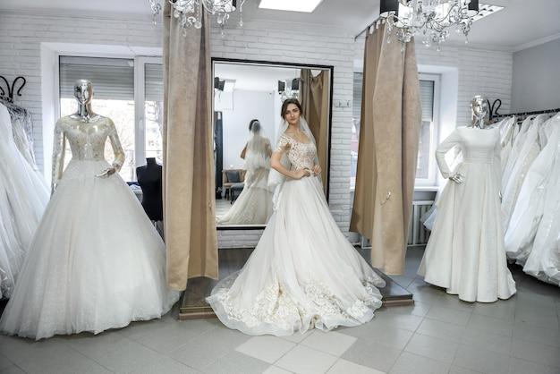 La sposa felice prova un abito da sposa in salone