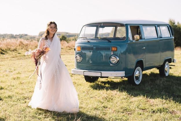 La sposa felice che porta un vestito rosa sta ballando vicino alla retro-automobile