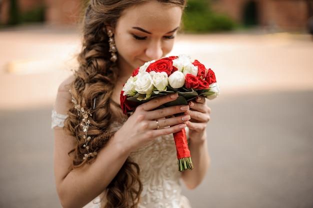 Sposa felice in un abito da sposa con un'acconciatura a treccia annusando un bouquet di rose rosse e bianche
