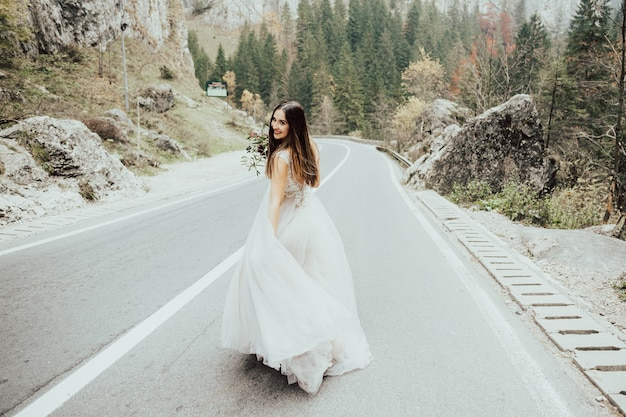 Sposa felice con un mazzo di fiori che cammina lungo una strada di montagna.