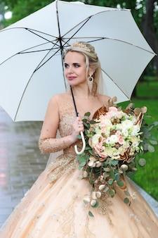 La sposa felice con un ombrello bianco sotto la pioggia, in estate nel parco. matrimonio all'aperto.