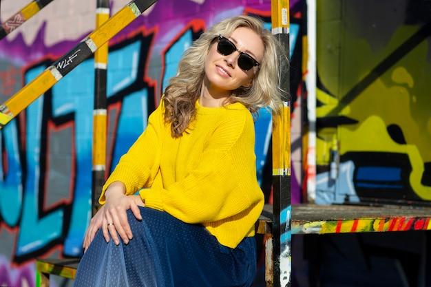 Felice giovane donna bionda alla moda brillantemente vestita in occhiali da sole sullo sfondo dei graffiti sulla strada