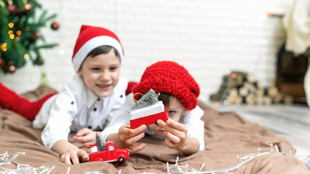 Fratelli felici in abiti natalizi stanno giocando sul pavimento vicino all'albero di natale a casa. idea di famiglia felice
