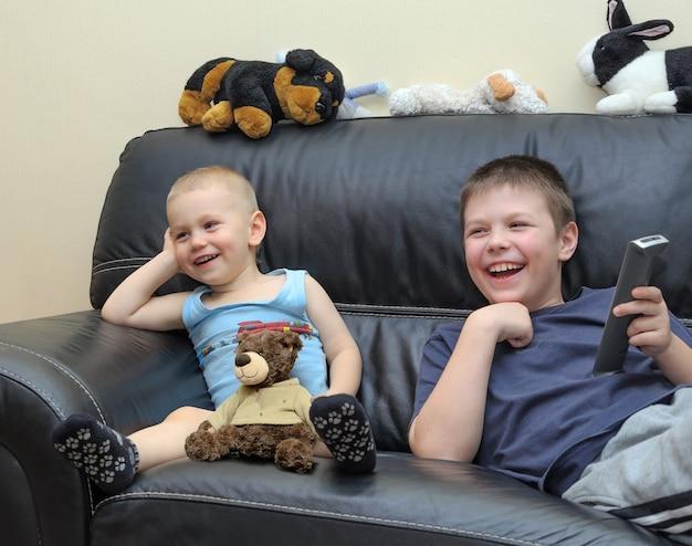 Fratelli felici che guardano la tv sul divano in pelle e si divertono insieme.