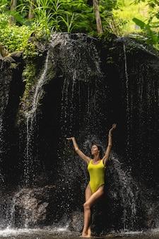 Felice ragazza bruna che tiene gli occhi chiusi mentre alza le braccia, in piedi sotto la cascata