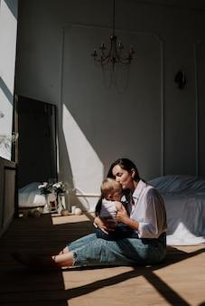 Felice mamma bruna e bambina che si baciano sul pavimento di legno sotto i raggi di luce
