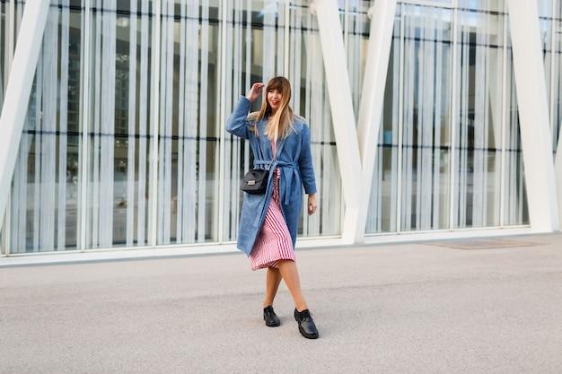 Donna castana felice in cappotto blu e vestito rosso che cammina lungo la strada moderna