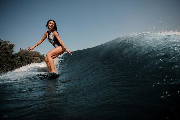Donna felice del brunette che pratica il surfing a bordo giù l'acqua blu