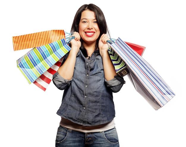 Felice donna bruna con borse della spesa su sfondo bianco