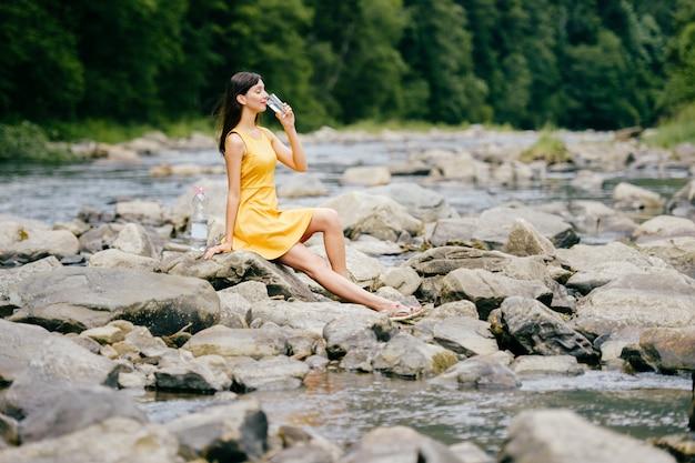 Brunette felice in vestito giallo che si siede sulle pietre