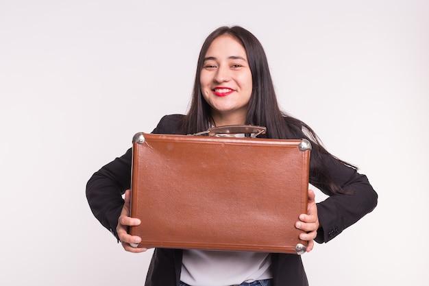 Felice giovane donna bruna con labbra rosse tenendo la valigia retrò su sfondo bianco.
