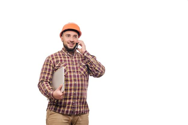 Operaio felice del costruttore nel casco arancione della costruzione protettiva che tiene un computer portatile e che parla sul telefono, isolato su fondo bianco. copia spazio per il testo. ora di lavorare.