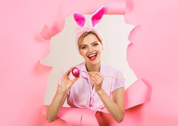 Uovo felice della pittura della donna del coniglietto. idee per le uova di pasqua. coniglio donna che guarda attraverso la carta.