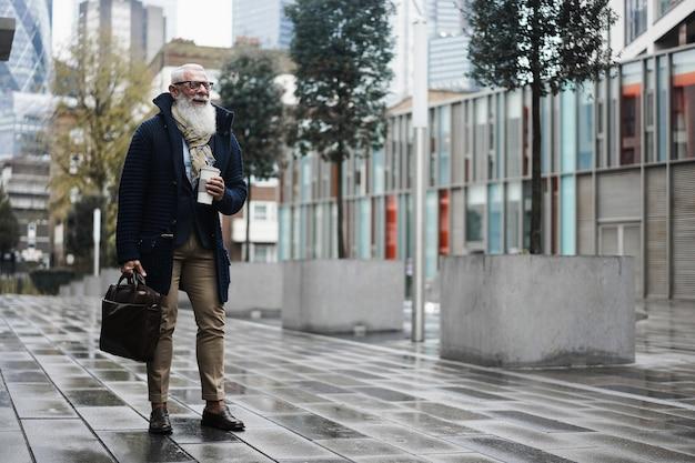 Uomo anziano felice dei pantaloni a vita bassa di affari che cammina per lavorare in città - fronte del fuoco