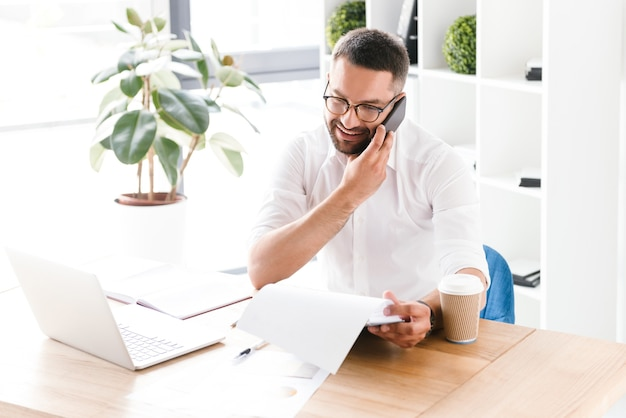 Happy business man 30s in camicia bianca parlando al cellulare e tenendo appunti con documenti cartacei, mentre è seduto al tavolo in ufficio