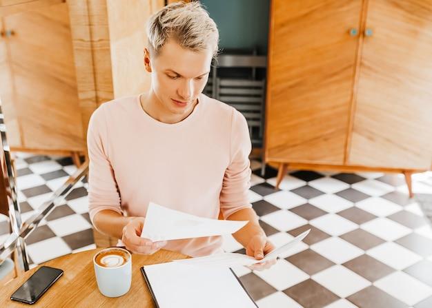 Uomo d'affari felice seduto alla caffetteria con laptop e documenti