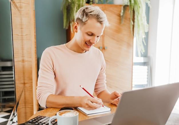 Uomo d'affari felice seduto alla caffetteria con laptop e smartphone.