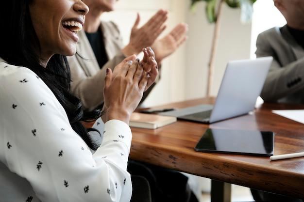 Uomini d'affari felici che applaudono nella sala conferenze