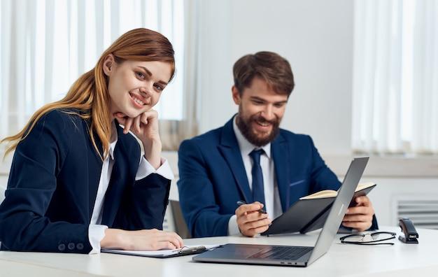 Gli uomini d'affari felici in ufficio con un laptop sono seduti al tavolo in una stanza luminosa. foto di alta qualità