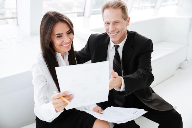Happy uomini d'affari seduti sul divano e guardando i documenti in ufficio