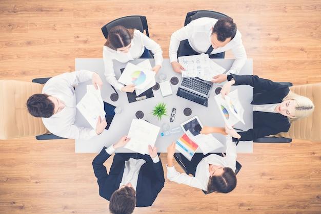 Gli uomini d'affari felici lavorano con le carte sul desktop. vista dall'alto Foto Premium