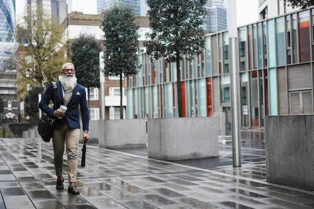 Uomo maggiore di affari felice che cammina per lavorare sulla giornata invernale piovosa - faccia di messa a fuoco