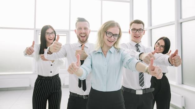 Squadra felice di affari che mostra i loro pollici in su. concetto di successo