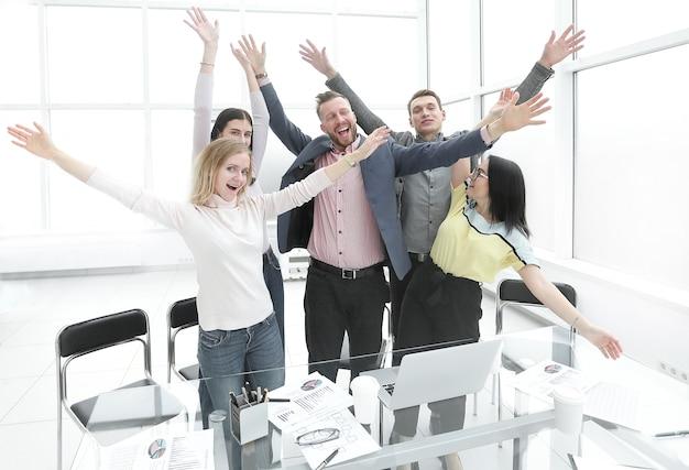 Happy business team in piedi in ufficio e mostrando il loro successo.foto con copia spazio