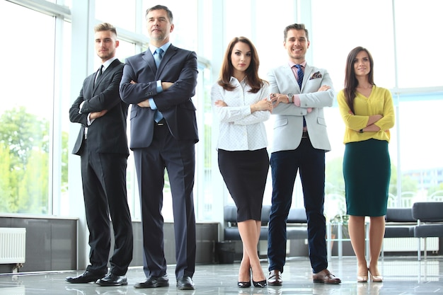 Happy business team con le braccia incrociate in ufficio.