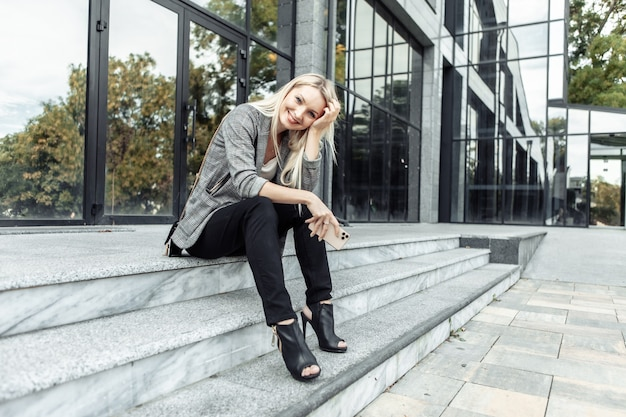 Happy business donna seduta sui gradini durante la pausa e tenendo lo smartphone sullo sfondo del centro business