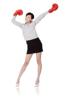 Donna felice di affari del vincitore sui guantoni da boxe, isolati su bianco.