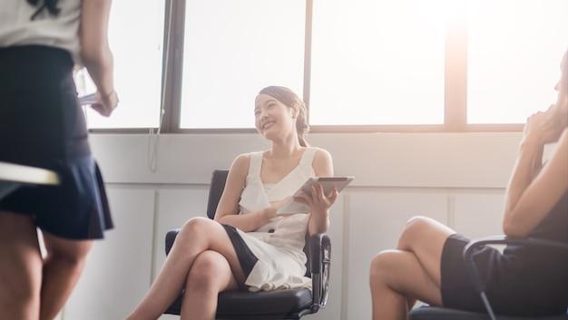 Donna felice di affari che lavora su una compressa e che discute del lavoro positivo che parla con collega