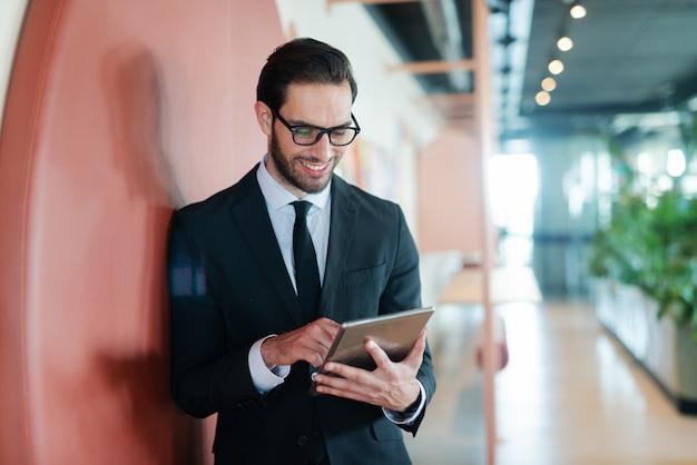 Felice imprenditore in abbigliamento formale in piedi contro il muro nel centro business e l'utilizzo di tablet per leggere la posta elettronica.