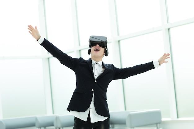 Uomo d'affari felice in un casco di una realtà virtuale in piedi in ufficio