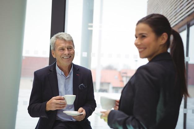 Uomo d'affari felice e donna di affari che mangiano caffè