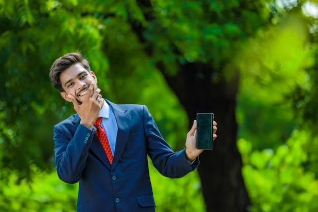 Felice imprenditore puntare il dito sullo schermo dello smartphone in bianco