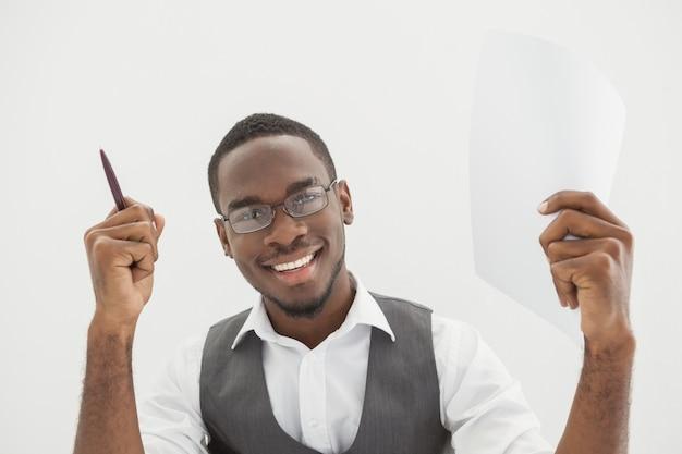 Uomo d'affari felice che mostra matita e pagina