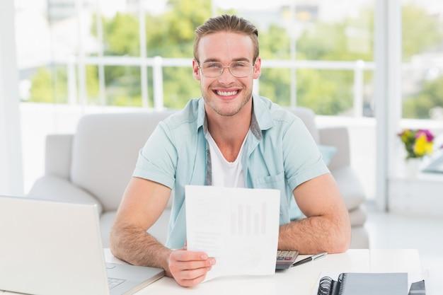 Uomo d'affari felice che si siede al suo documento della holding dello scrittorio