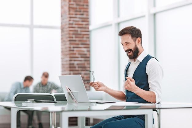 Felice uomo d'affari seduto alla sua scrivania in ufficio.concetto aziendale