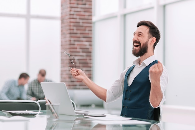 Felice imprenditore seduto alla scrivania in ufficio