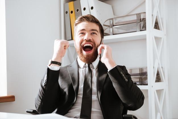 L'uomo d'affari felice che parla dal telefono e fa il gesto del vincitore.