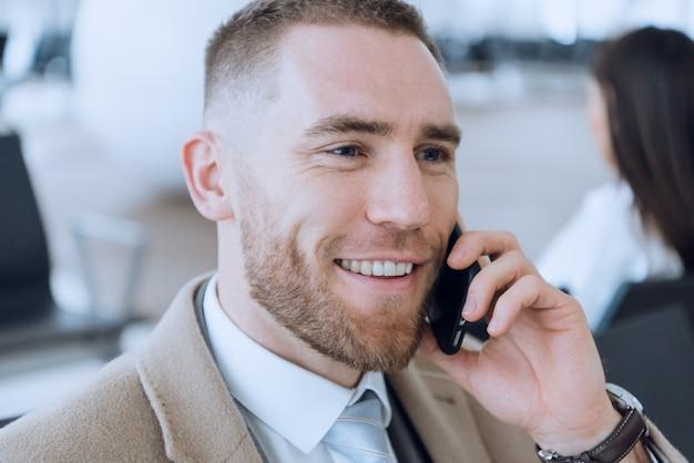 Uomo d'affari felice che parla sul cellulare al salotto aspettante dell'aeroporto