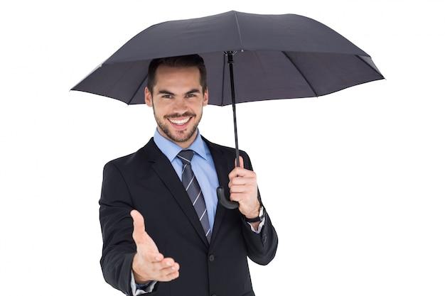 Uomo d'affari felice sotto la stretta di mano d'offerta dell'ombrello