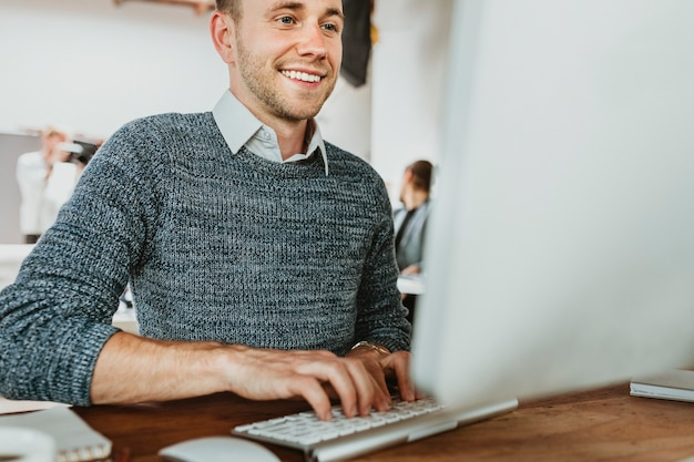Uomo d'affari felice che usa un computer