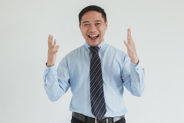 Uomo d'affari felice che indossa camicia e cravatta blu che sorride alla macchina fotografica