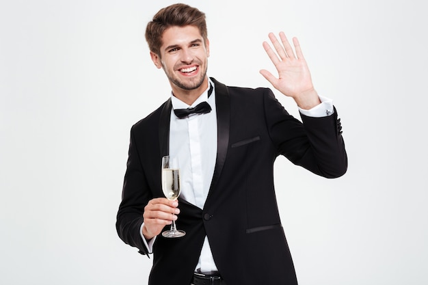 Uomo d'affari felice con champagne. salutando