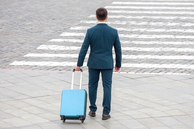 L'uomo d'affari felice con la valigia da viaggio ha attraversato l'incrocio segnalato della strada della città