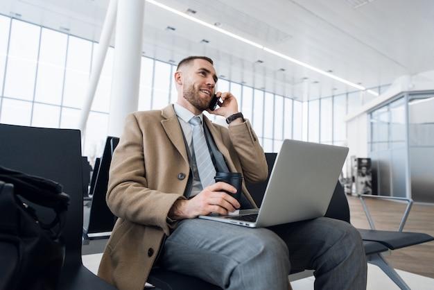 Uomo d'affari felice che lavora al computer portatile e che parla sul cellulare al salotto aspettante dell'aeroporto.