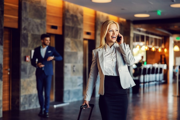 Felice imprenditrice in viaggio d'affari camminando nella hall dell'hotel e parlando al telefono. lusso, affari, telecomunicazioni, prima cosa, euforia