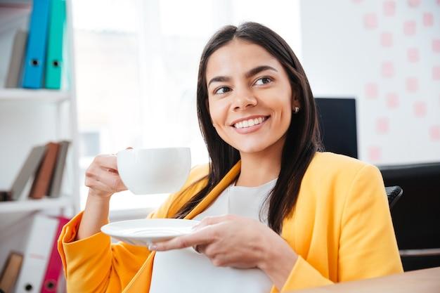 Felice imprenditrice che beve il tè in ufficio
